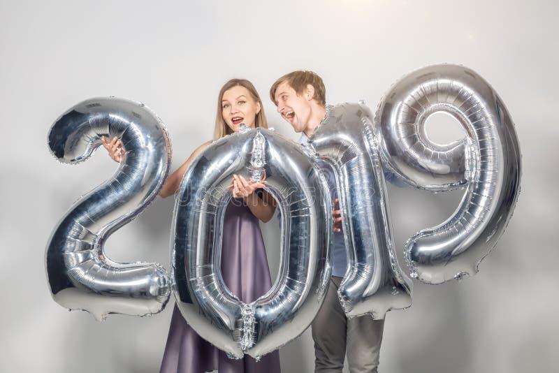 Det nya 2019 året är det kommande begreppet - den lyckliga unga mannen och kvinnan rymmer för att försilvra kulöra nummer på vit  royaltyfria bilder