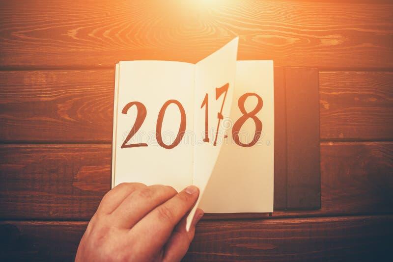 Det nya året 2018 är det kommande begreppet Handen bläddrar notepadarket på trätabellen 2017 är roterande, 2018 öppnar royaltyfri bild