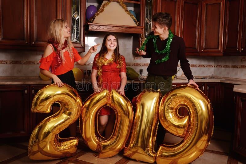 Det nya 2019 året är kommande Grupp av gladlynta ungdomarsom bär guld- kulöra nummer och att ha gyckel på partiet arkivfoton