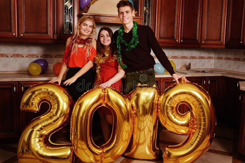 Det nya 2019 året är kommande Grupp av gladlynta ungdomarsom bär guld- kulöra nummer och att ha gyckel på partiet royaltyfri fotografi
