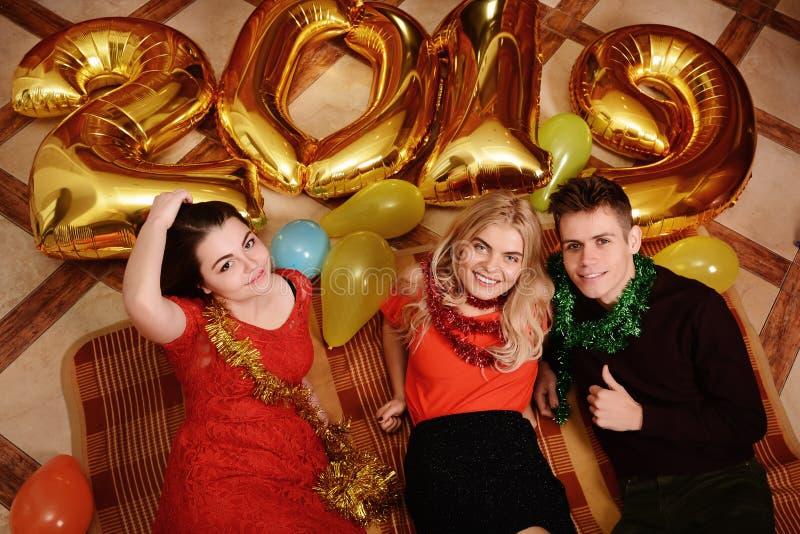 Det nya 2019 året är kommande Grupp av gladlynta ungdomarsom bär guld- kulöra nummer och att ha gyckel på partiet royaltyfri foto