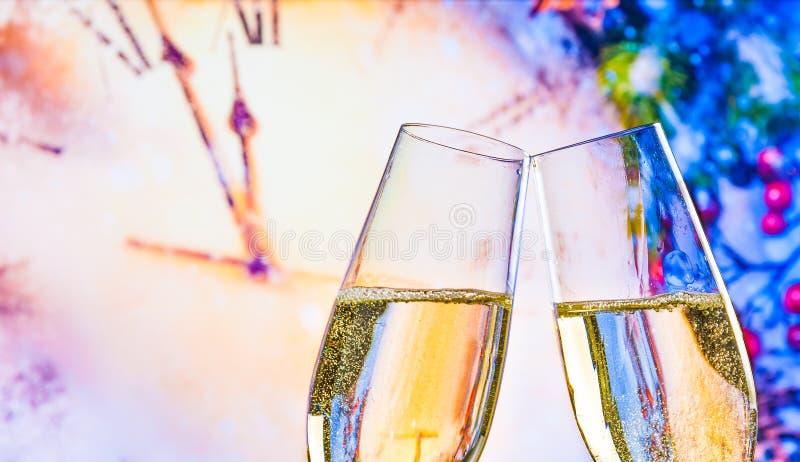 Det nya året eller jul på midnatt med champagneflöjter gör jubel på klockabakgrund arkivbild
