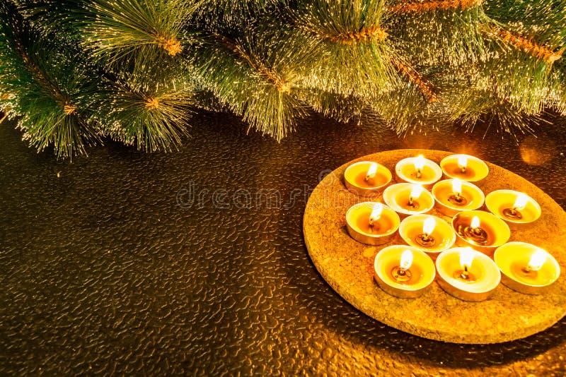 Det nya året och jul, sörjer gröna konstgjorda på en svart bakgrund i ljuset av vaxstearinljus Gula varma enkla handlag, mig arkivfoto