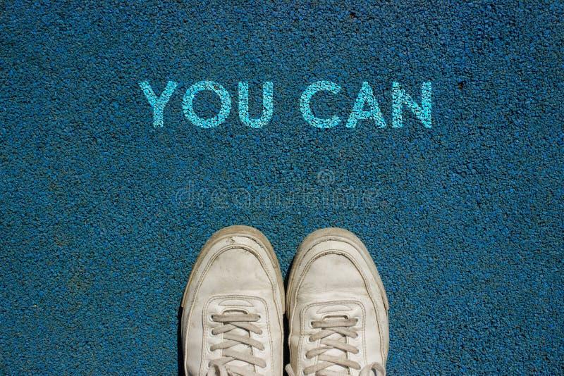 Det nya livbegreppet, sportskor och ordet KAN DU skriftligt på gångbanajordning, Motivational slogan royaltyfri fotografi