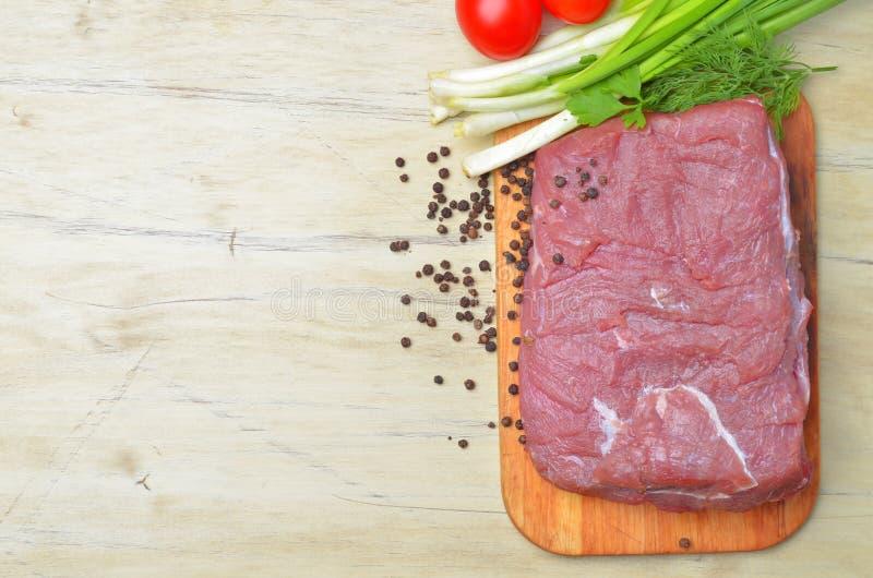 Det nya rå stycket av kött ligger på köksvart tavla arkivbilder