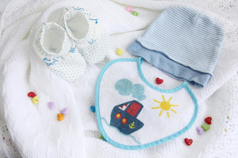 Det nyfödda stickade plagg behandla som ett barn byten, hatten och haklappen på virkad vit bakgrund för filt med färgrika hjärtor royaltyfri bild