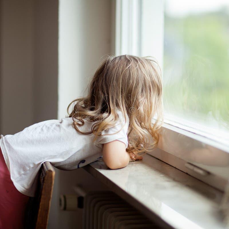 Det nyfikna gulliga liten flickaanseendet på en stol på fönstret, blondin krullar arkivfoton