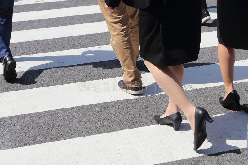 Det oidentifierade folket lägger benen på ryggen korsningen gata arkivfoto