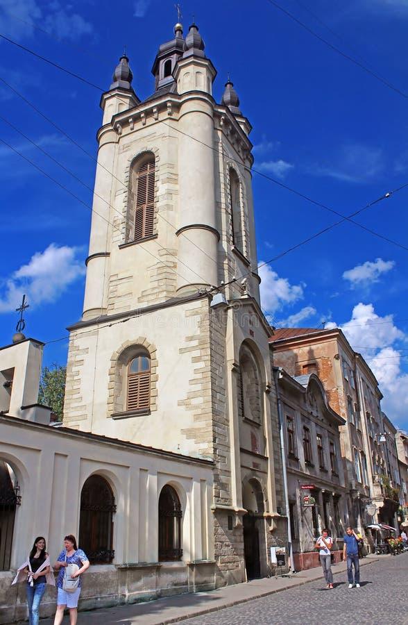 Det oidentifierade folket near klockatornet av den armeniska domkyrkan av antagandet av Mary i Lviv, Ukraina arkivbilder