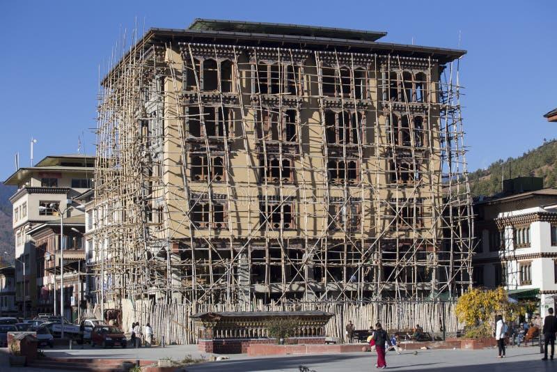 Det oidentifierade folket ser en byggnad under konstruktion i Paro, Bhutan fotografering för bildbyråer