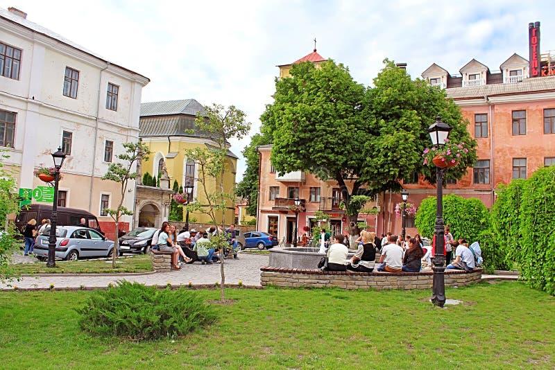 Det oidentifierade folket vilar på gatan i Kamianets-Podilskyi, Ukraina arkivfoton