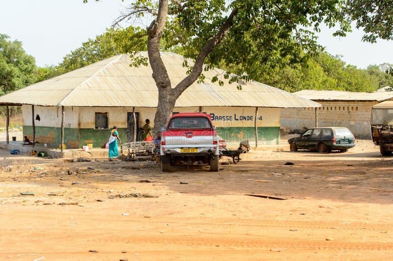 Det oidentifierade lokala folket går nära byggnaden i en by I fotografering för bildbyråer