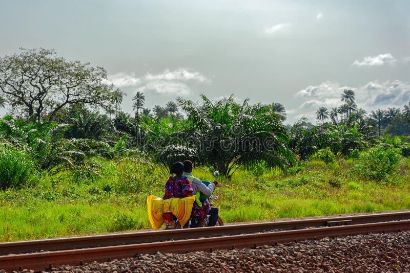 Det oidentifierade lokala folket rider en moped på den typiska röda vägen för jordGuinea bygd längs järnväg av bauxit som bryter  arkivbilder