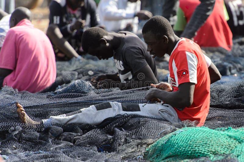 Det oidentifierade senegalesiska folket gör fisknät på kustnollan arkivbilder