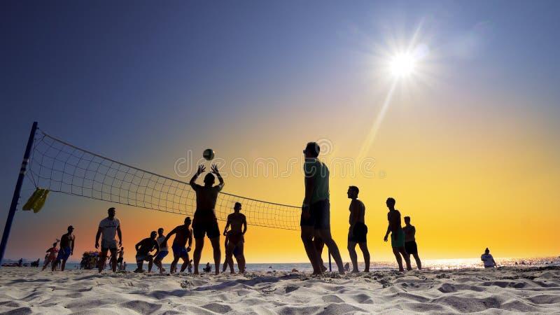 Det oigenkännliga konturfolket spelar strandvolleyboll på solnedgången arkivfoto
