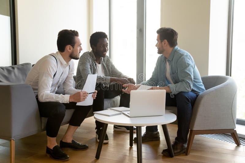 Det olika manliga arbetarlaget lyssnar till chefmentorn som diskuterar skrivbordsarbete fotografering för bildbyråer