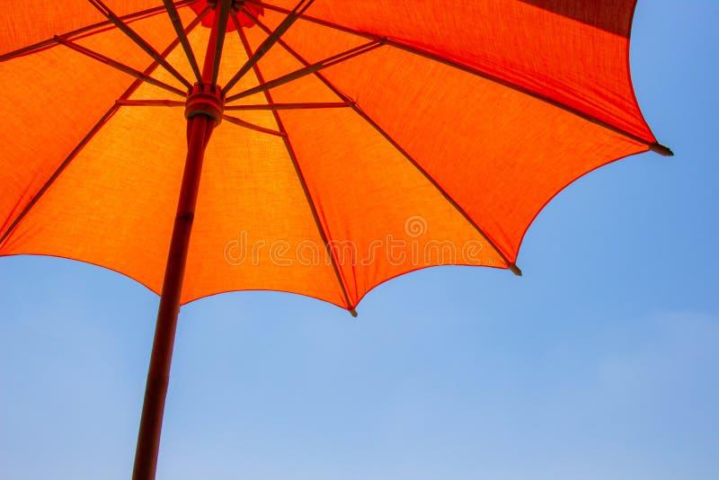 Det orange färgstrandparaplyet gjorde av trä för skyddat solljus med en ljus bakgrund för blå himmel royaltyfria bilder