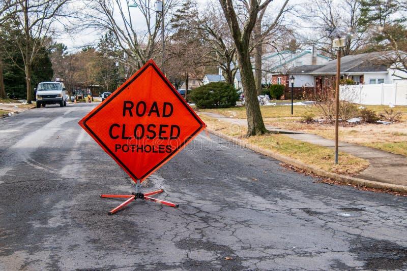 Det orange triangulära vägmärket på en liten förorts- gata, som säger vägen, stängde gropar arkivfoton