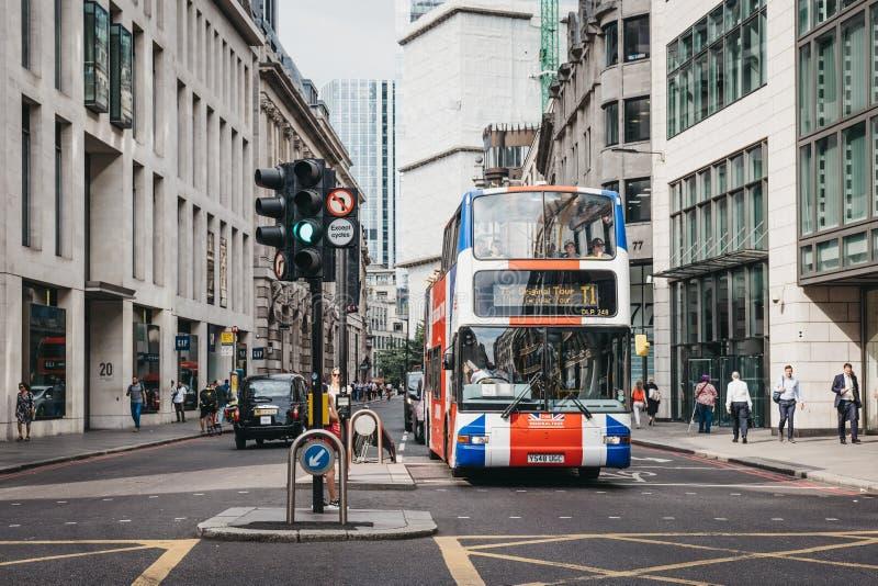 Det original- turnerar bussen som målas som Union Jack på en gata i staden av London, UK royaltyfri bild
