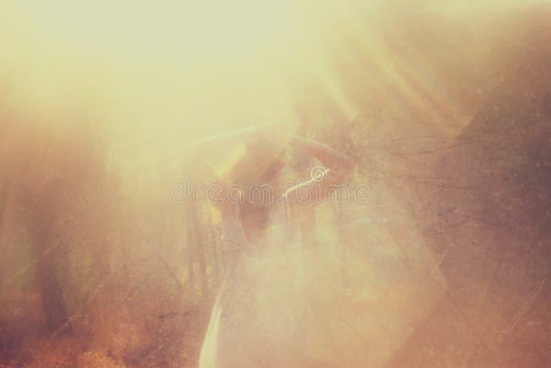Det overkliga fotoet av anseendet för den unga kvinnan i skogbild textureras och tonas Drömlikt begrepp arkivfoton