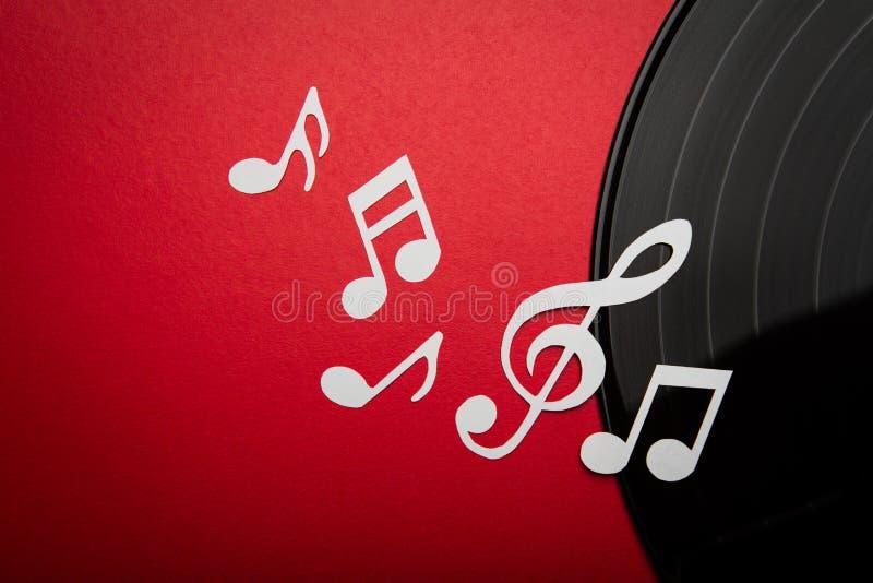 Det pappers- snittet av musik noterar på svart diskett för album för vinylrekordlp med kopierar utrymme för text royaltyfri bild