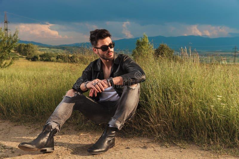 Det placerade bärande läderomslaget för mannen ser bort för att sid royaltyfri foto