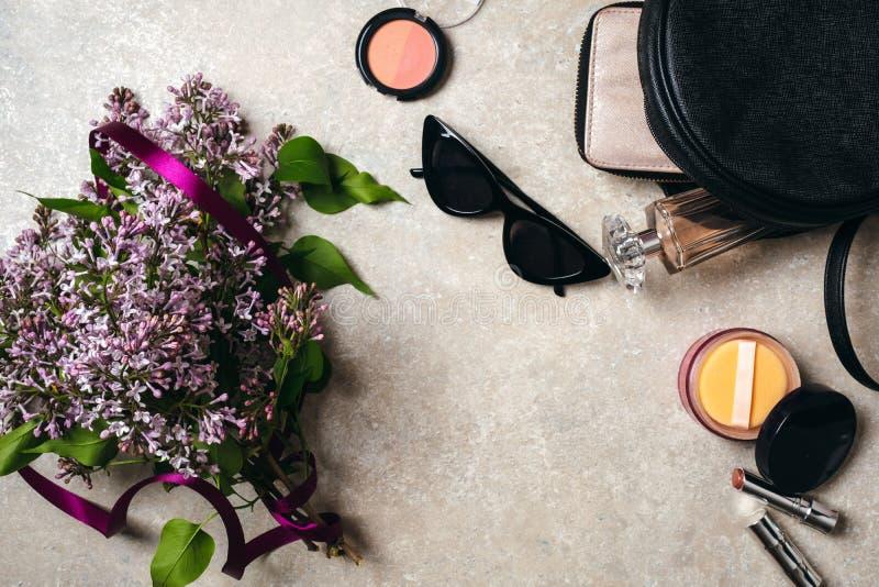 Det plana lekmanna- moderna minsta hem- workspaceskrivbordet med lila blommor för våren, solglasögon, piskar påsen, plånboken, kv arkivfoto