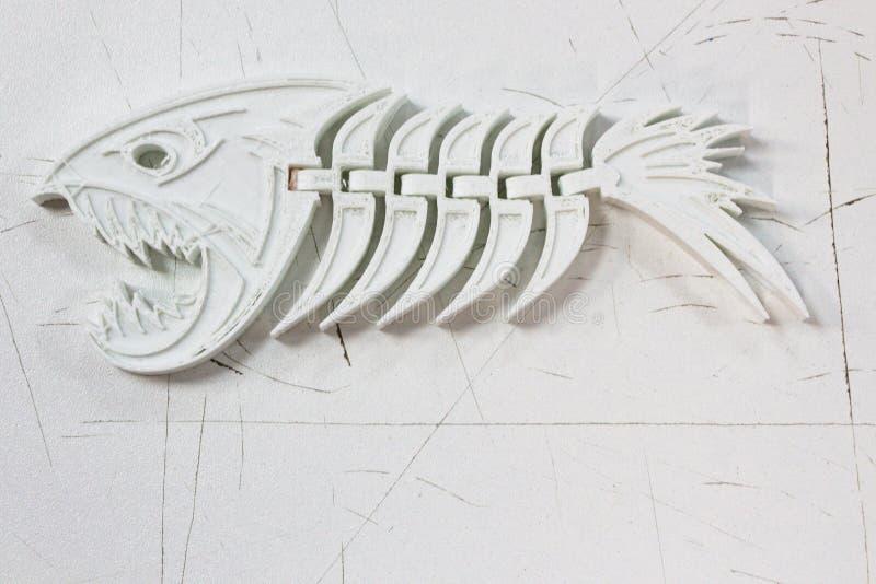 Det plast- skelettet av fisken ligger på en vit bakgrund Det skrivs ut på en skrivare 3d royaltyfri bild
