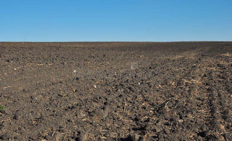 det plogade jordbruks- fertila fältet smutsar royaltyfri foto
