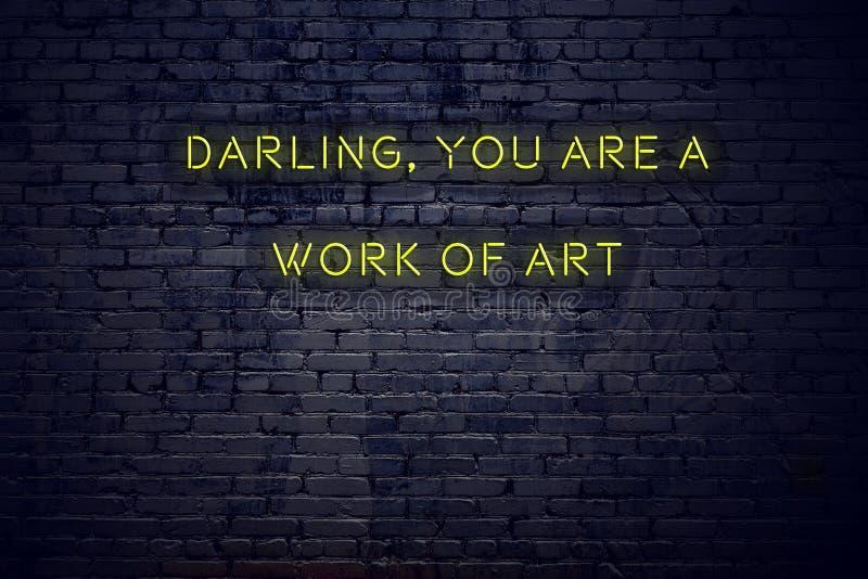 Det positiva inspirerande citationstecknet på neontecken mot älskling för tegelstenvägg är du ett konstverk arkivfoto