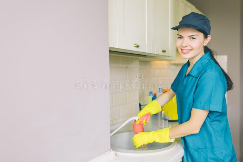 Det positiva och trevliga rengöringsmedlet står på vasken och ser på kamera Hon tvättar vattenröret Flickan gör ren i kök från royaltyfri fotografi