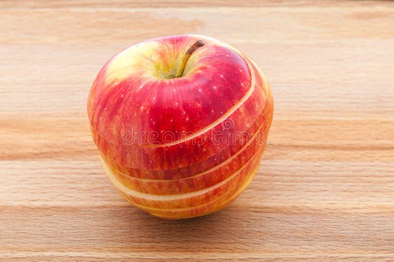 Det röda äppleslut-UPS snittet rånar förbi på en träskärbräda arkivfoto