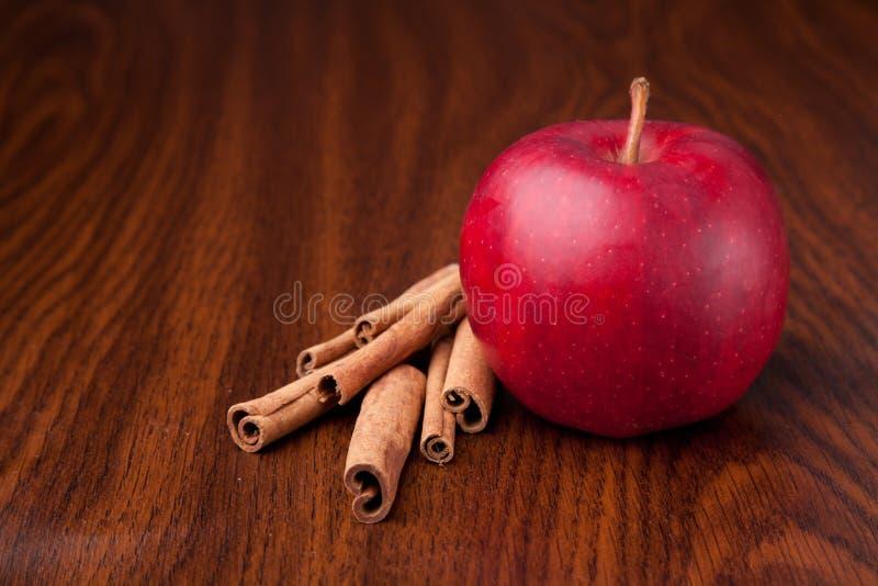 Det röda äpplet på det trämörkret bordlägger med pinnar av kanelen royaltyfri fotografi