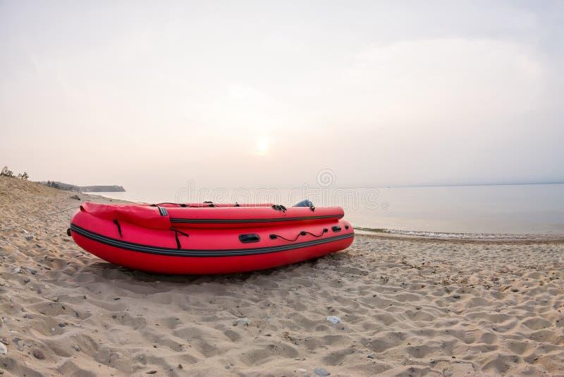 Det röda fartyget står på den sandiga stranden av havet på solnedgången royaltyfria bilder