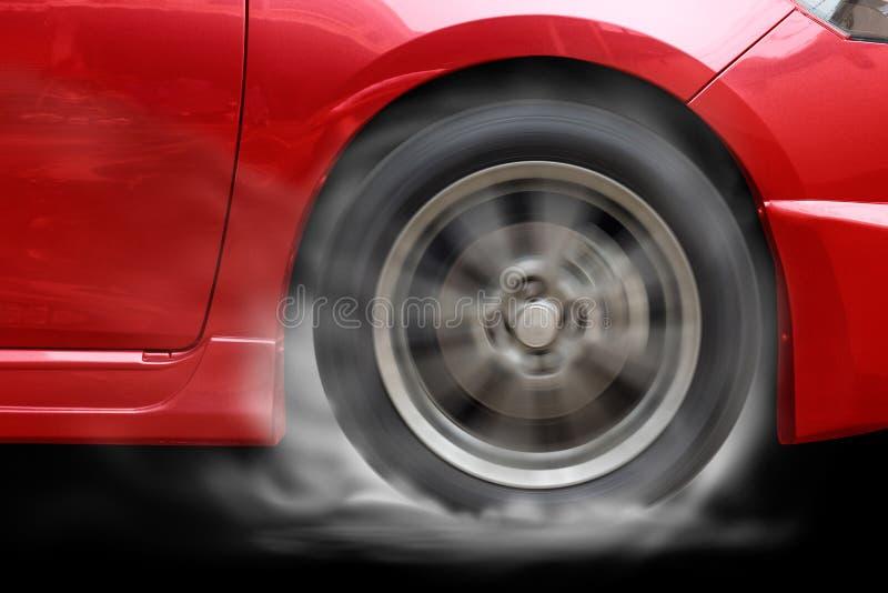 Det röda hjulet för snurret för springa för bil bränner gummi på golv fotografering för bildbyråer