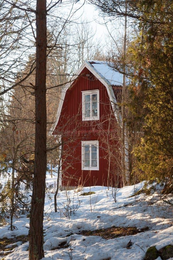 Det röda målade svenska trähuset i ett wintry landskap royaltyfri fotografi