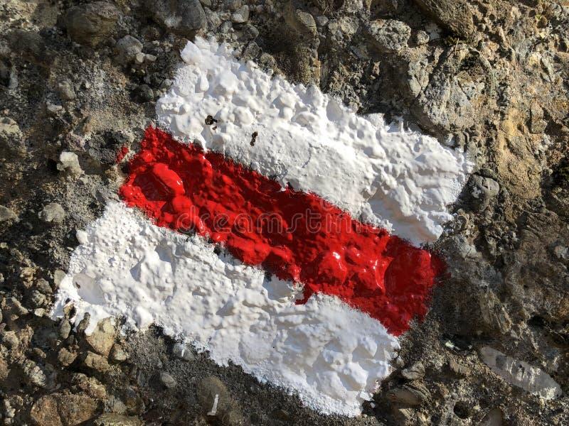 Det röda och vita tecknet som målas på, vaggar att markera den fotvandra slingan eller den schweiziska markeringen för bergslinga royaltyfria foton