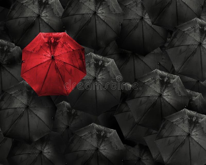 Det röda paraplyet med vattendroppe står ut från folkmassan av många bl royaltyfria bilder