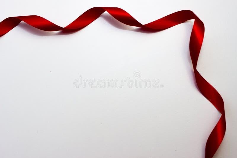 Det röda satängbandet är i ett hörn av sidan fotografering för bildbyråer