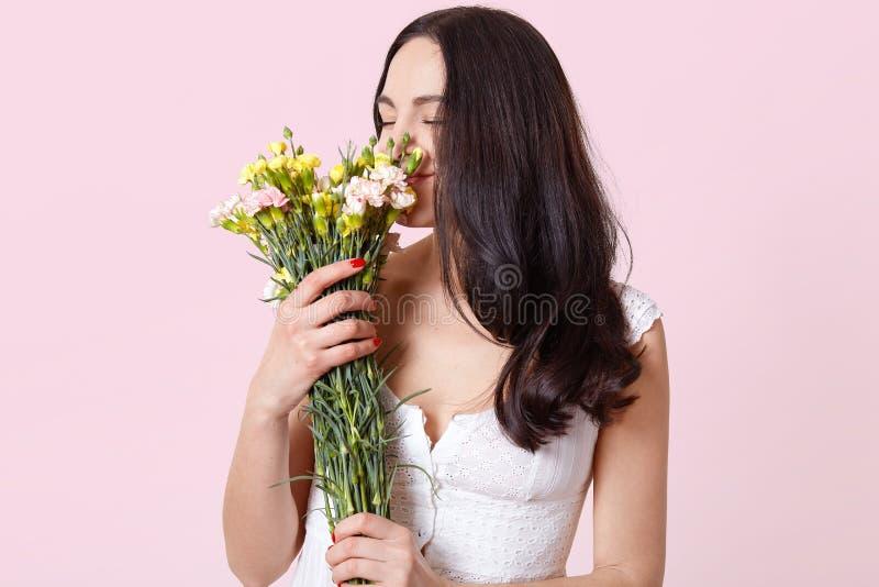 Det raka mjuka s?ta anseendet f?r den unga damen f?r brunetten och att rymma h?rliga blommor i b?da h?nder som k?nner deras v?rlu royaltyfri bild