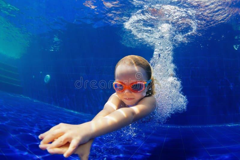 Det roliga barnet i skyddsglasögon dyker i simbassäng royaltyfri fotografi