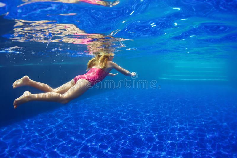 Det roliga barnet i skyddsglasögon dyker i simbassäng royaltyfri bild