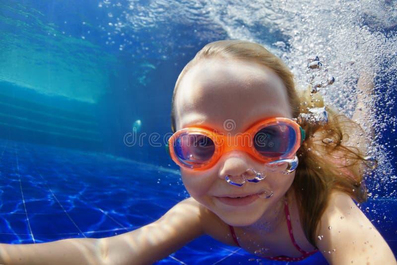 Det roliga barnet i skyddsglasögon dyker i simbassäng royaltyfria foton