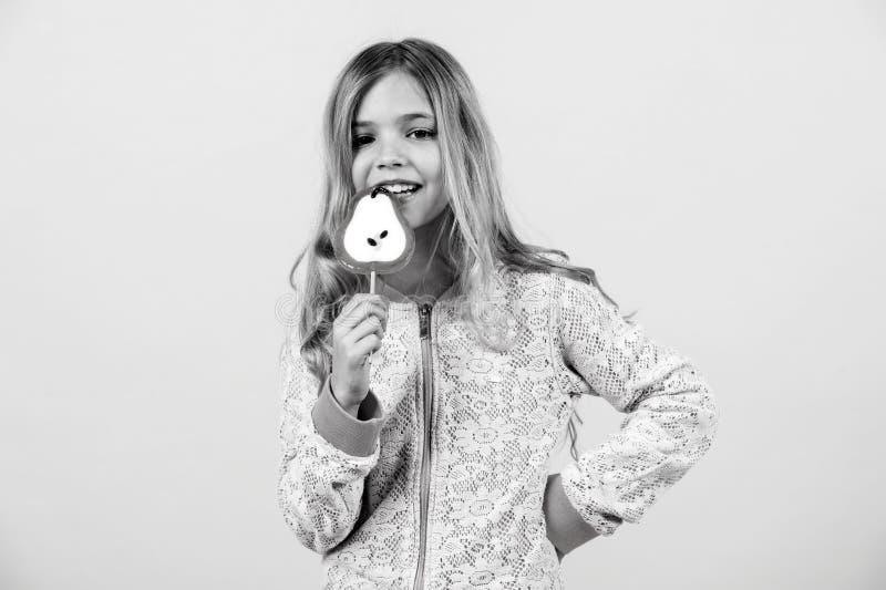 Det roliga barnet med godisklubban, den lyckliga lilla flickan äter den stora sockerklubban, unge äter sötsaker förvånat barn med royaltyfri foto