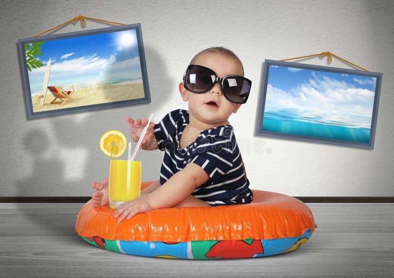 Det roliga barnet vilar på simningcirkeln hemma, som på stranden Vaca royaltyfri bild