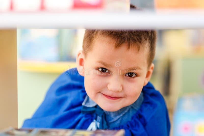 Det roliga femåriga barnet ser ut fönstret i dagis royaltyfri fotografi