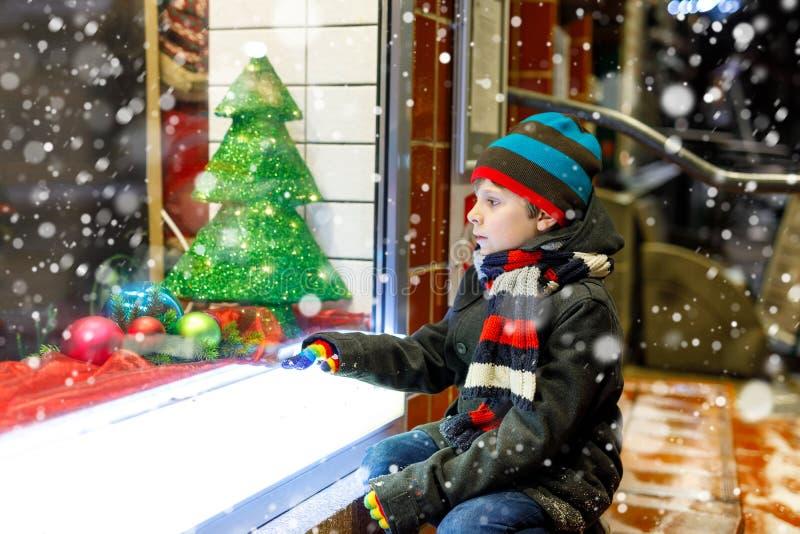 Det roliga lyckliga barnet i modevinter beklär danandefönstershopping som dekoreras med gåvor, xmas-träd arkivbild