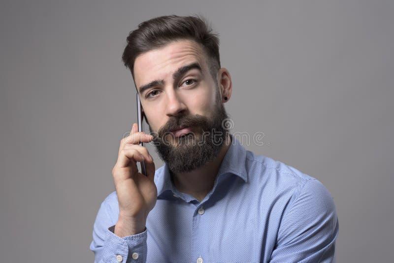 Det roliga lyftta ögonbrynet förbryllade ansiktsuttryck av den unga affärsmannen som talar på telefonen som ser kameran arkivbild