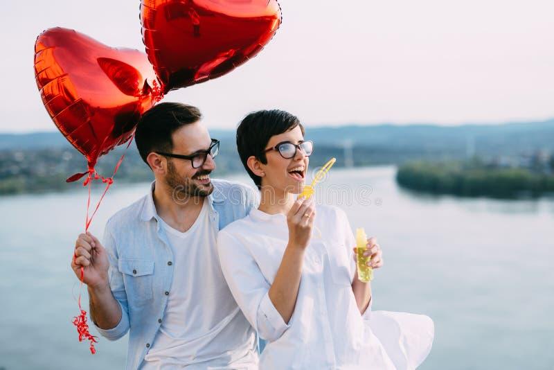 Det romantiska barnet kopplar ihop att datera som är utomhus-, och att blåsa bubblor royaltyfri foto