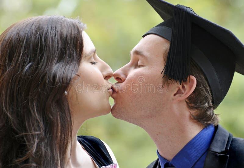 Det romantiska barnparet som kysser efter man, avlägger examen universitetet royaltyfria bilder